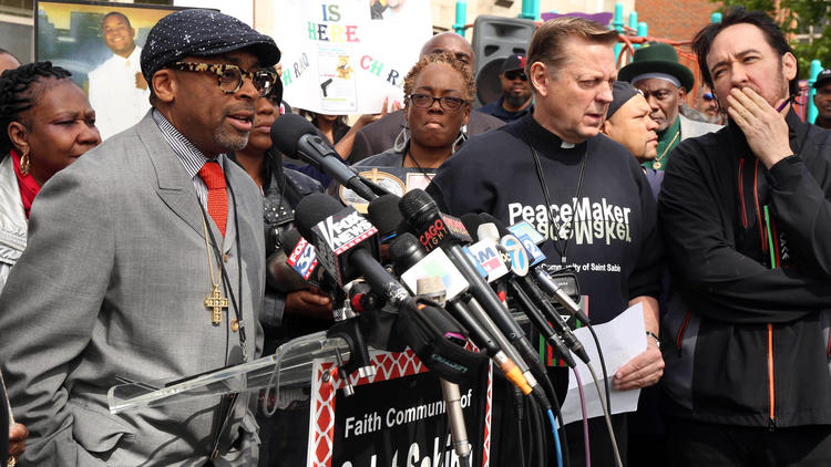 "Spike Lee, left, speaks outside St. Sabina Catholic Church in Chicago on May 14, 2015, about his planned movie ""Chiraq."" Lee, the Rev. Michael Pfleger, second from right, actor John Cusack, right, and parents of victims of gun violence spoke to a crowd in the church's courtyard. (Phil Velasquez, Chicago Tribune)"